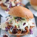 BBQ pulled pork sandwich with coleslaw on top and BBQ sauce