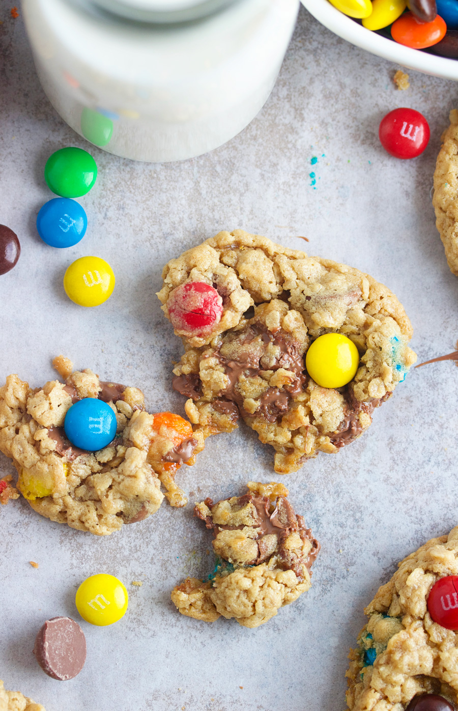 overhead shot of a monster cookie broken open with a glass of milk and extra M&Ms laying by it