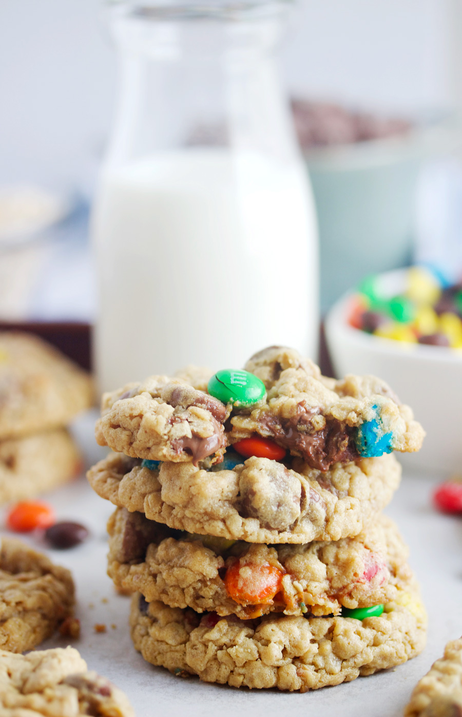 stack of three monster cookies with a glass of milk behind them