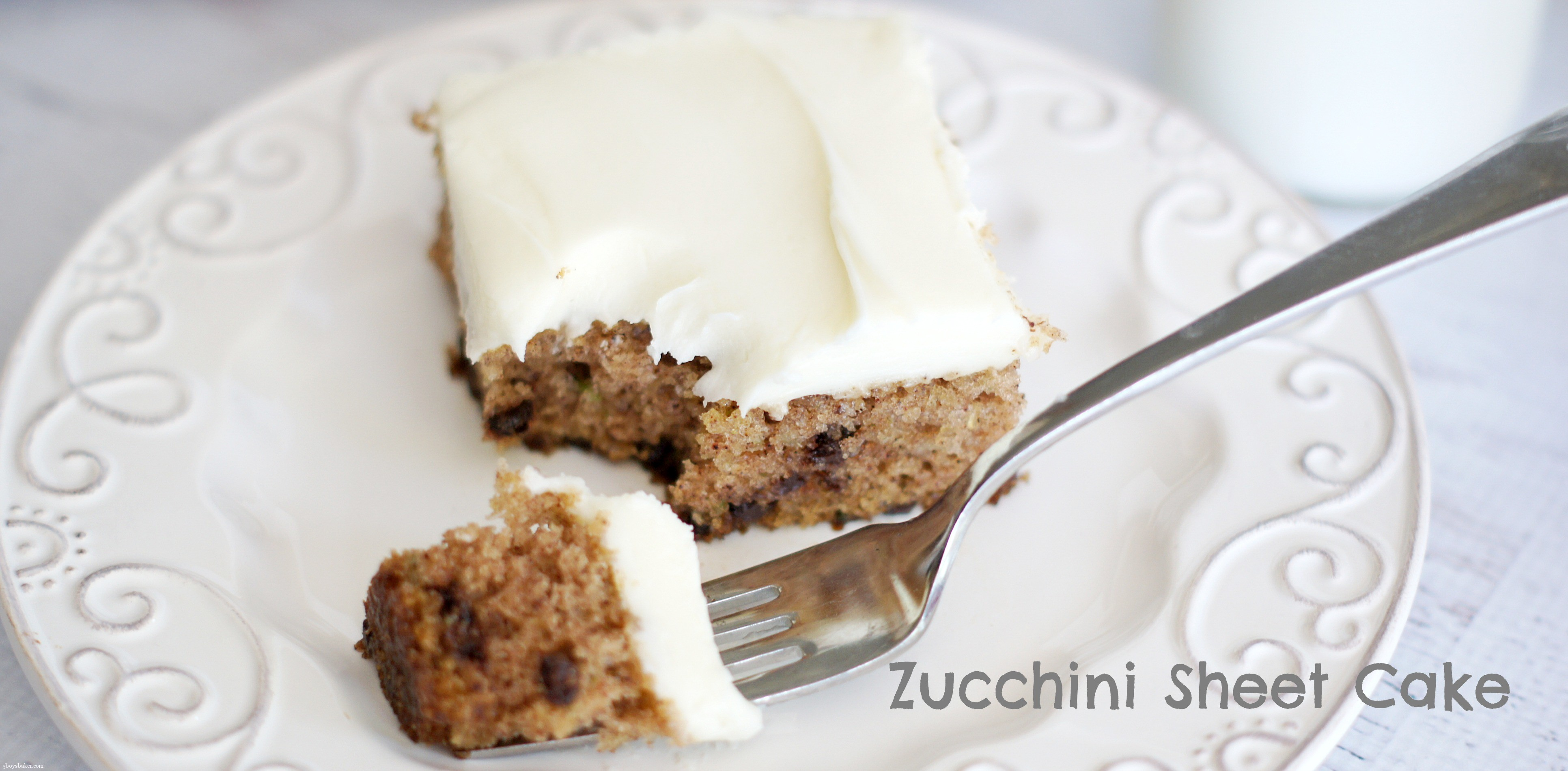 piece of zucchini sheet cake with cream cheese frosting on a white plate with a bite on a fork