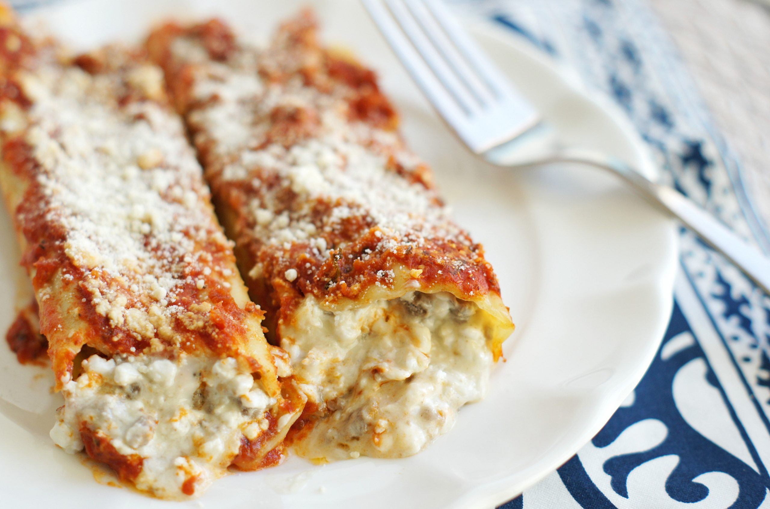 White plate with two pieces of manicotti on it.