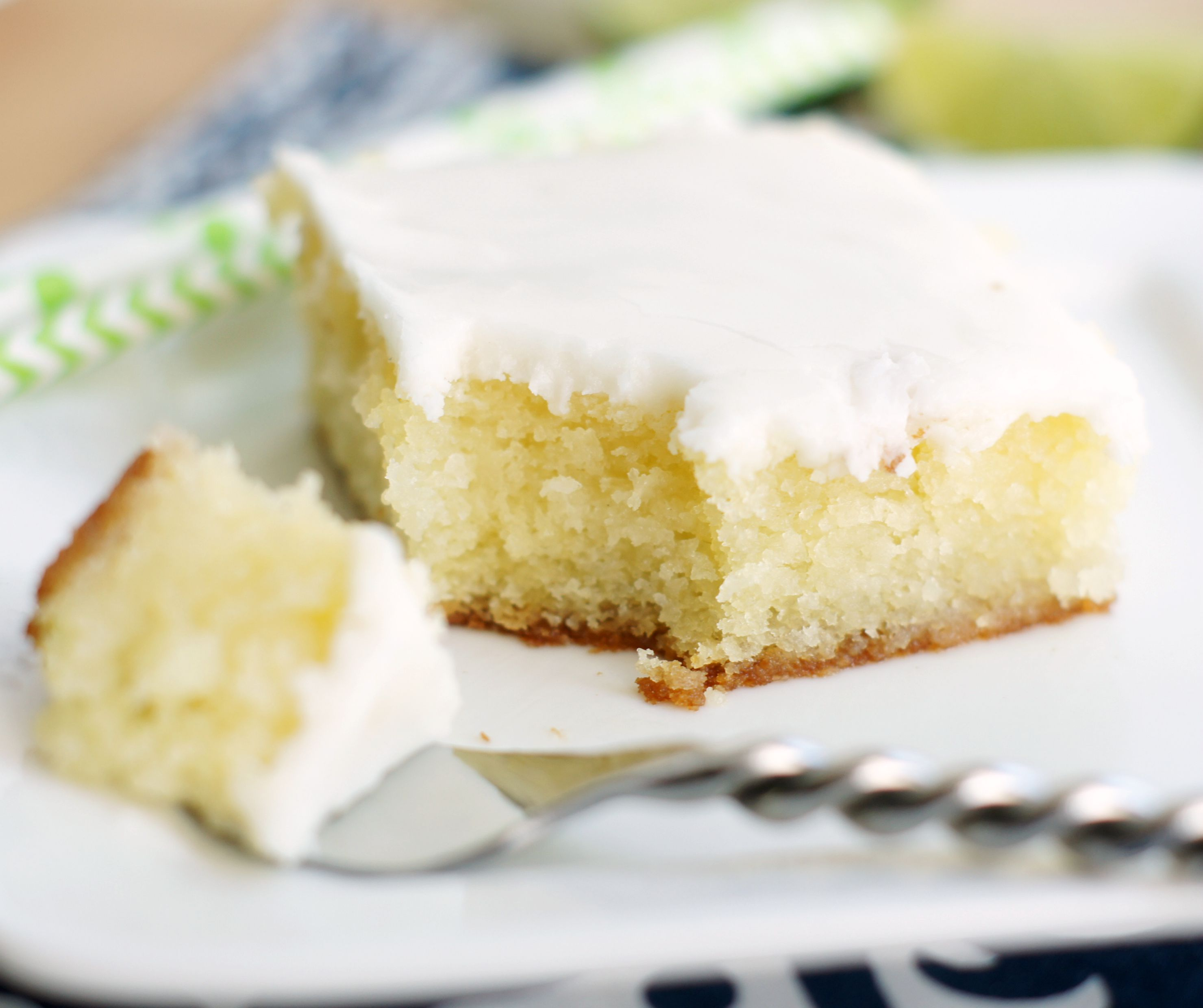Up close shot of a piece of glaze lime cake with a bite on a fork