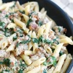 skillet with penne sausage dinner in it
