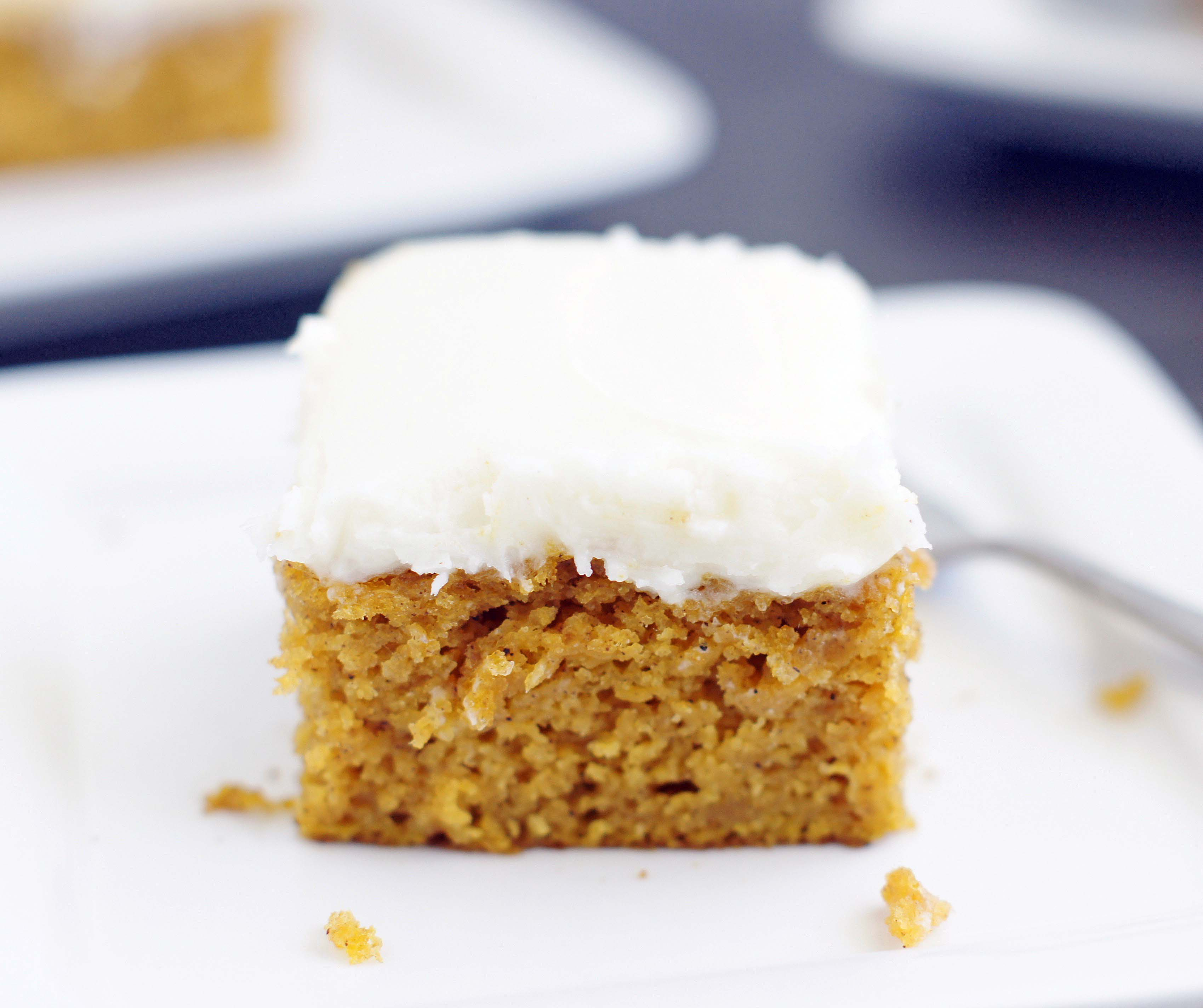 Single pumpkin bar with cream cheese frosting sitting on a plate