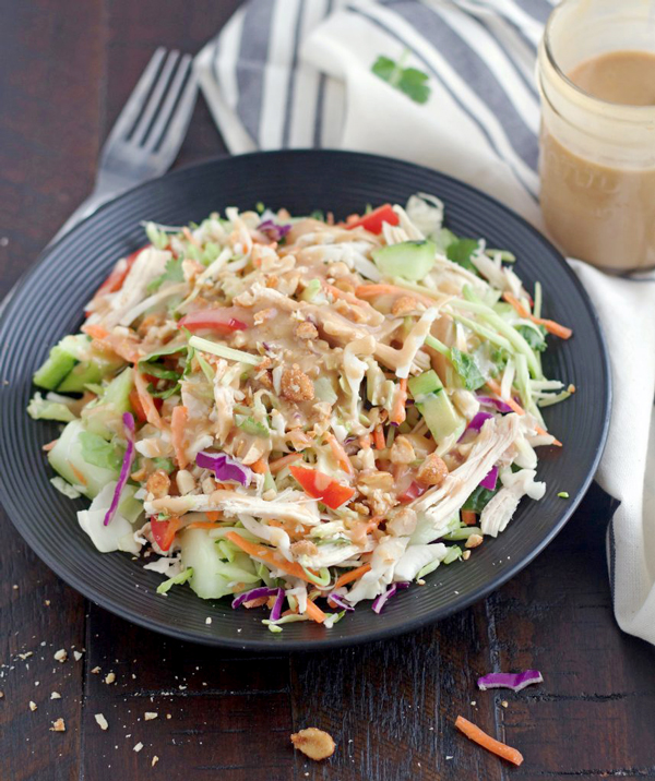 A bowl of Thai Chicken Crunch Slaw Salad with dressing being poured on it