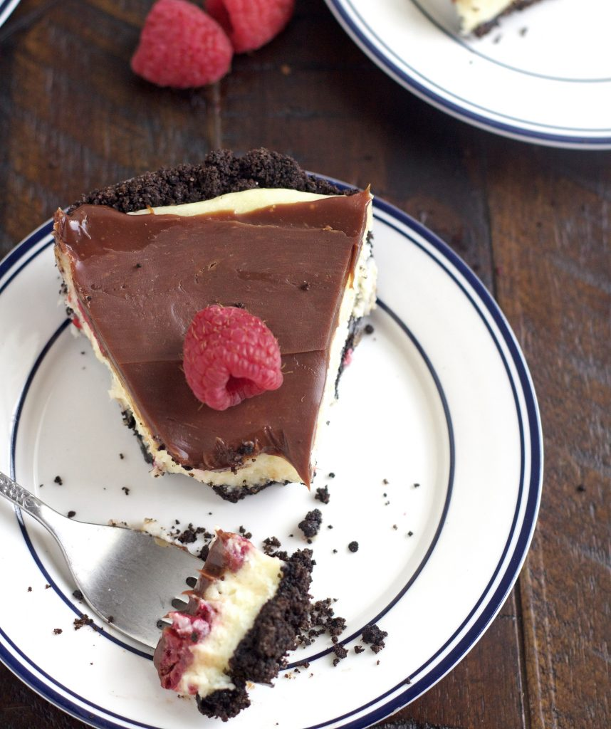 piece of raspberry cream cheese pie with chocolate ganache on a white plate with a bite on a fork