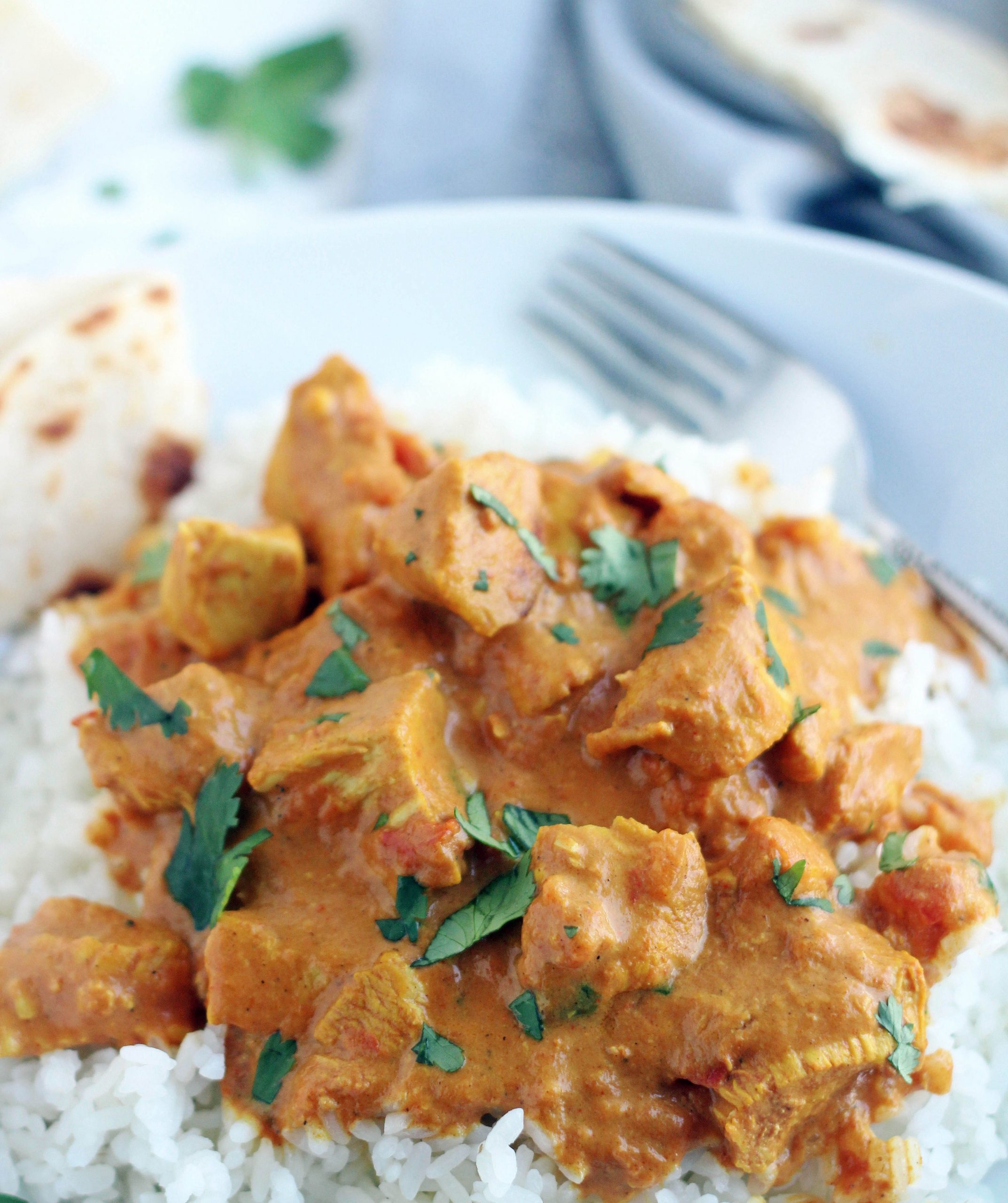 plate of instant pot butter chicken with flat bread on the side