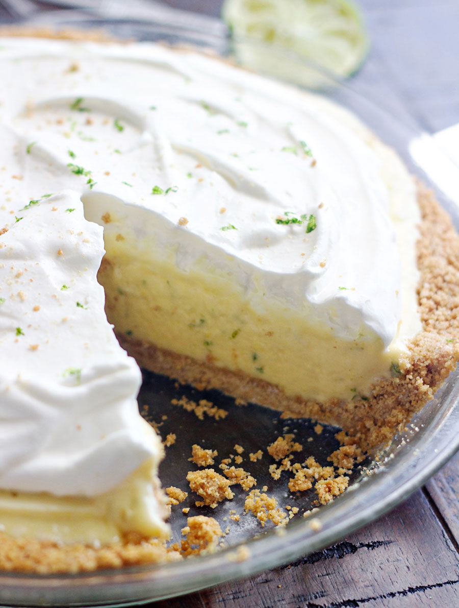 Up close shot of a key lime pie with a slice cut out.