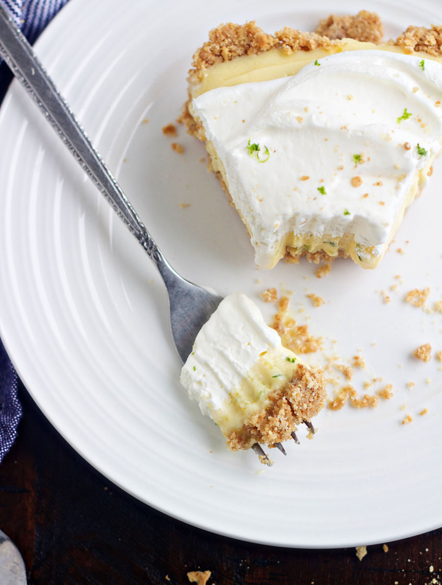 Slice of key lime pie with a bite on a fork