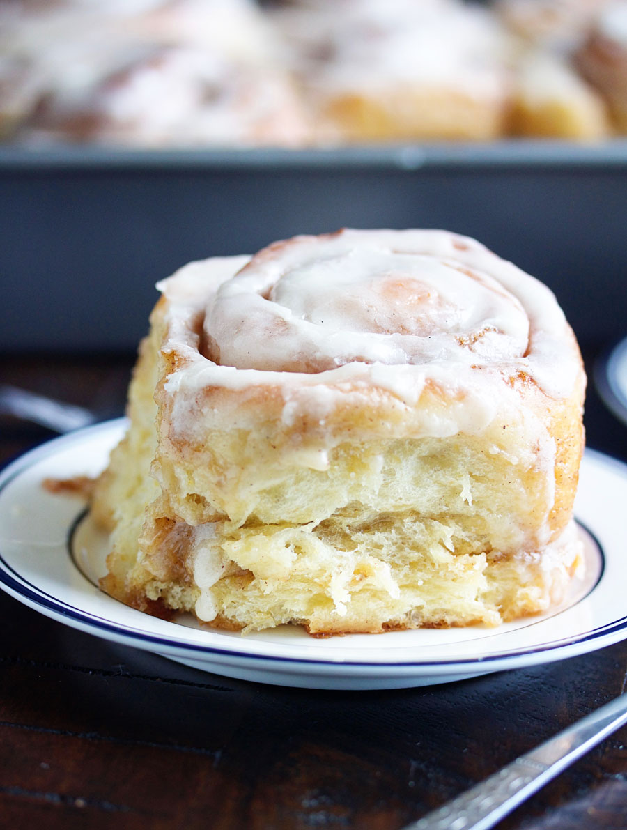 A cinnamon roll with vanilla bean buttercream on a plate