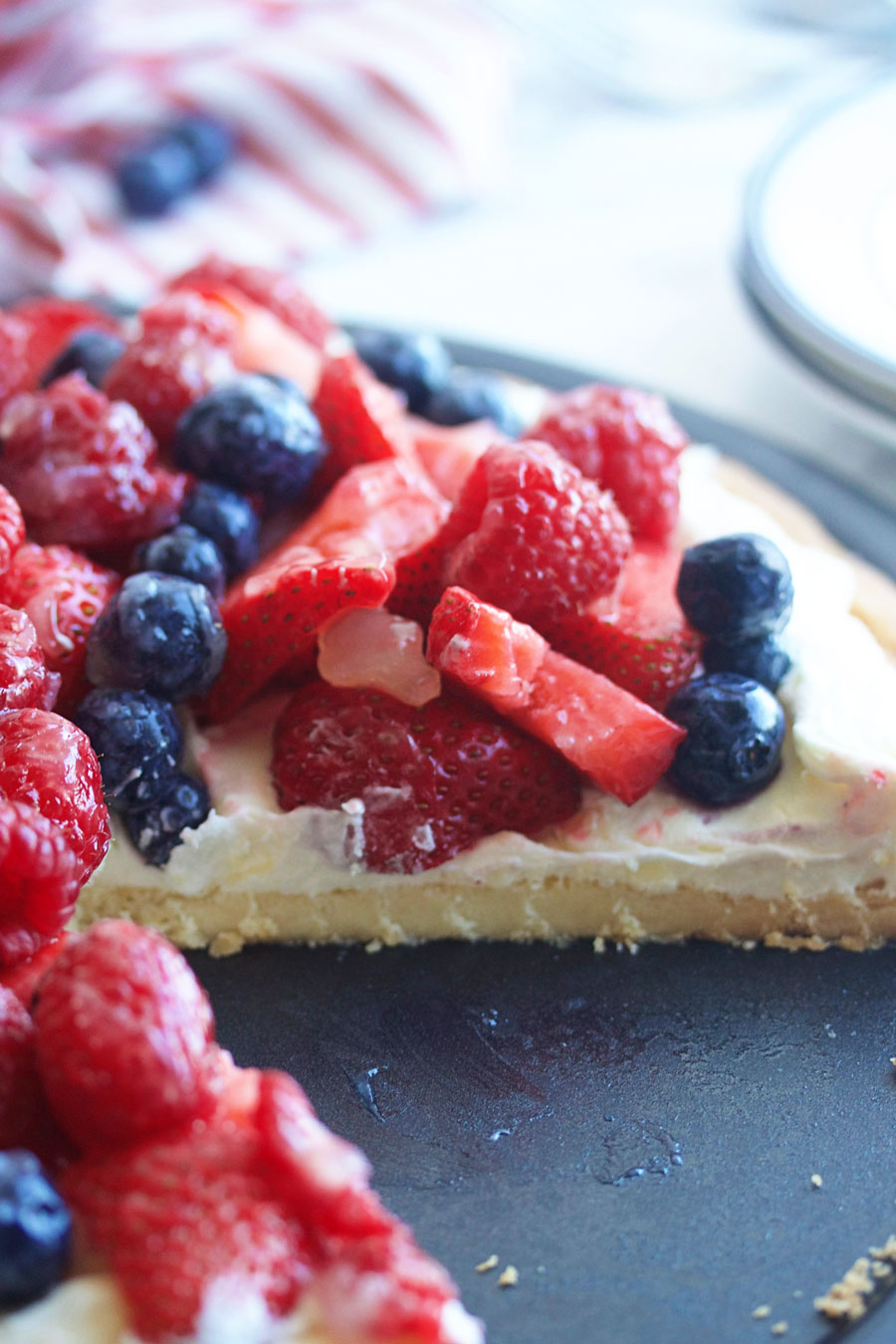 Vanilla cream fruit tart with a slice take out of it