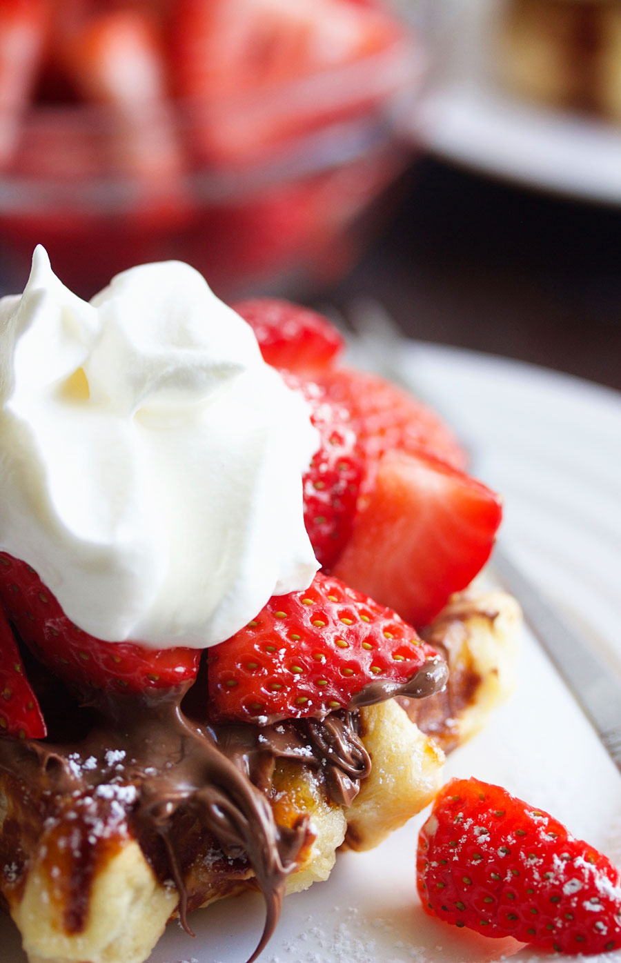 up close shot of a liege waffle with nutella, strawberries and whipped cream