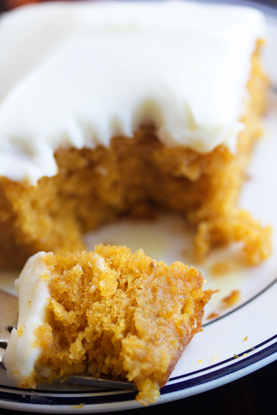 up close shot of a piece of pumpkin poke cake with cream cheese frosting