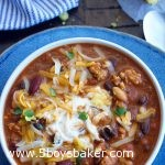 over head shot of turkey pumpkin chili in a bowl with cornbread