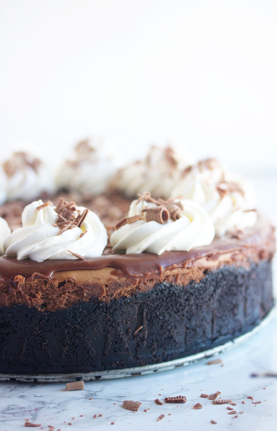 Side shot of a whole chocolate cheesecake with Oreo crust
