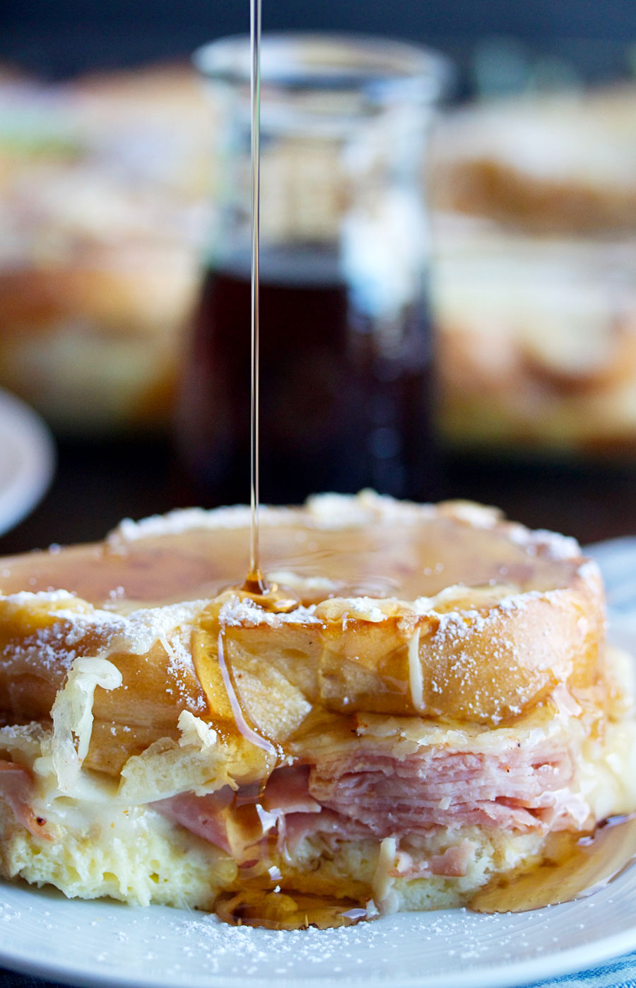 Monte Cristo Casserole with syrup being poured over a piece