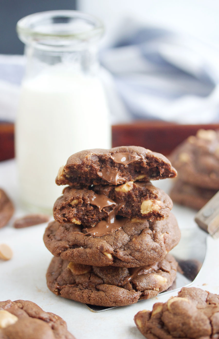 A stack of chocolate chocolate chunk peanut butter cookies with a glass of milk behind them.