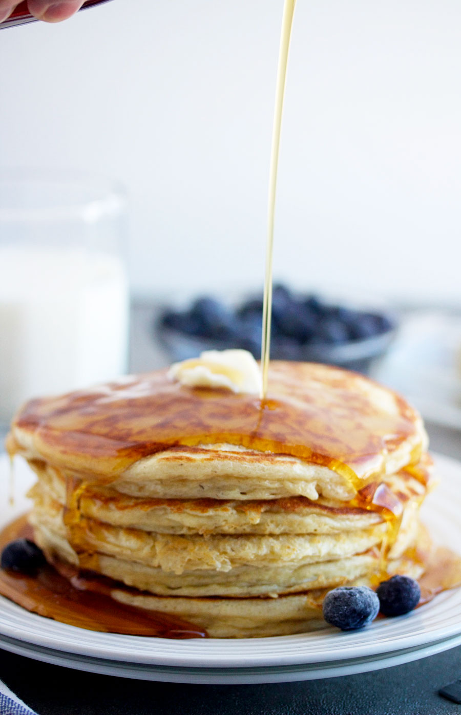 stack of cottage cheese pancakes with syrup being poured over the top