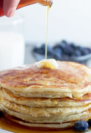 stack of cottage cheese pancakes with syrup being poured on them