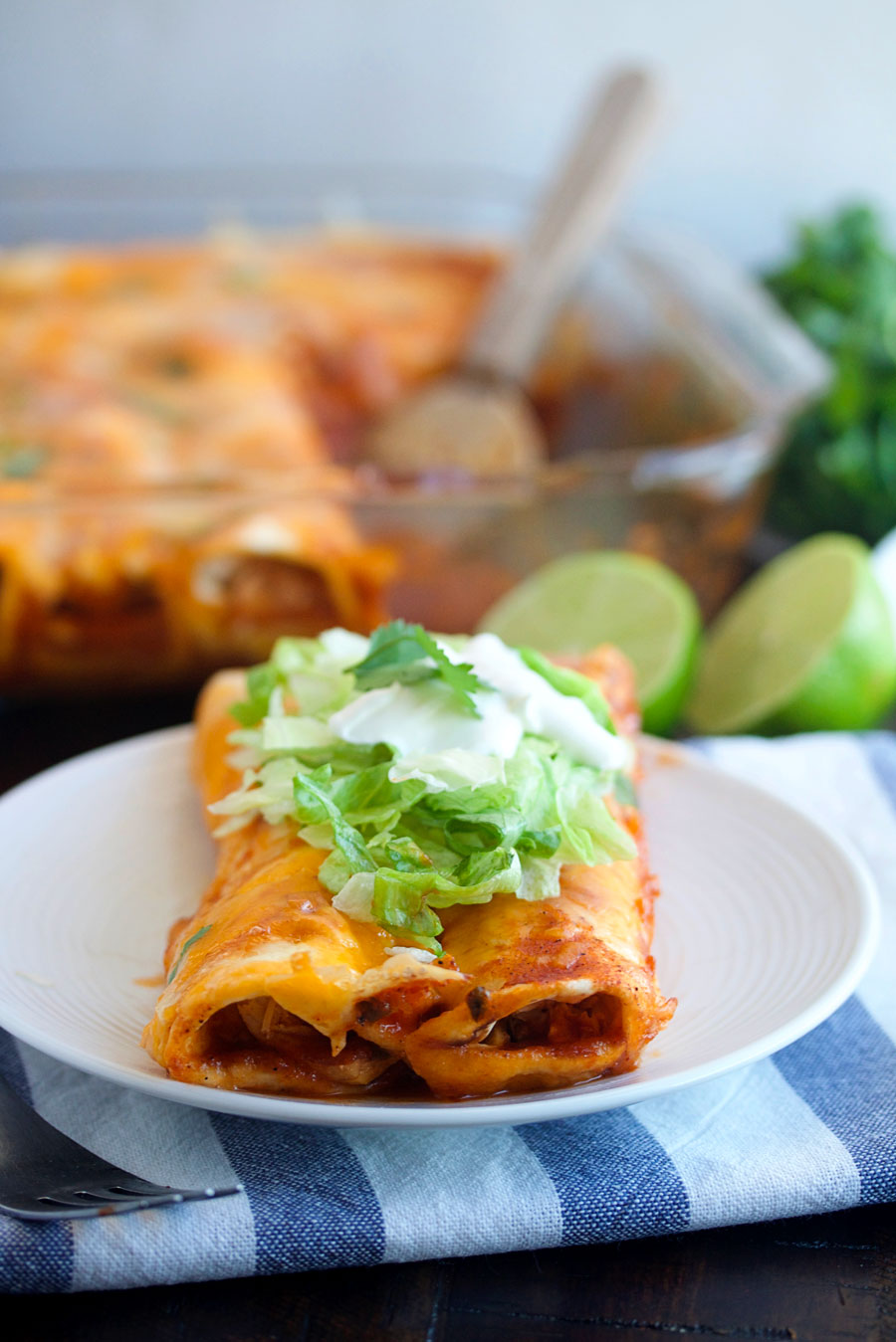 a plate with two instant pot chicken enchiladas on it.
