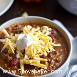 up close shot of a bowl of instant pot chili with cheese and sour cream on top
