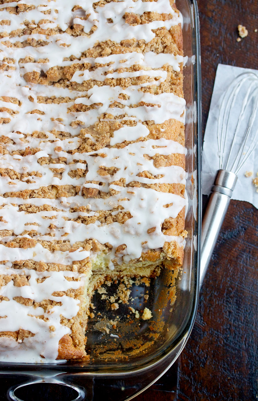 Overhead shot of a pan of sour cream coffee cake with cinnamon streusel with a piece cut out