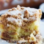 a piece of sour cream coffee cake with cinnamon streusel on a white plate with a bite on a fork