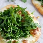 a white pizza with arugula on top