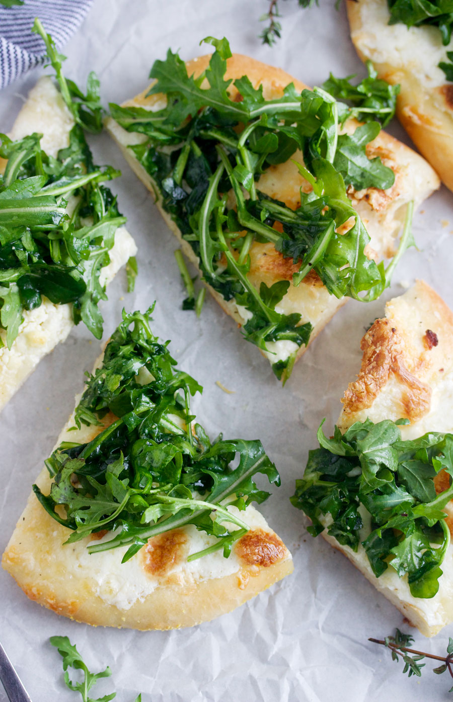 overhead shot of slices of white pizza with arugula