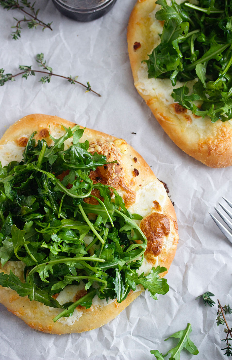 overhead shot of white pizzas with arugula on parchment paper