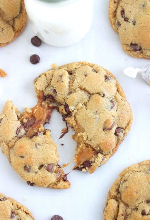 Overhead shot of a caramel stuffed chocolate chip cookie broken in half with caramel oozing out.