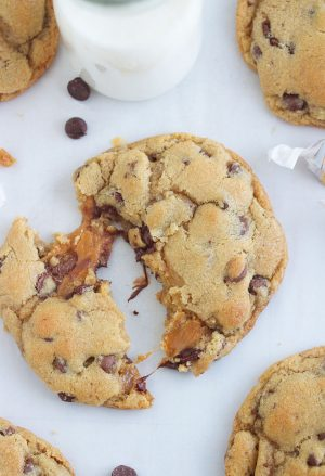 overhead shot of a caramel stuffed chocolate chip cookie broken in half with caramel oozing out