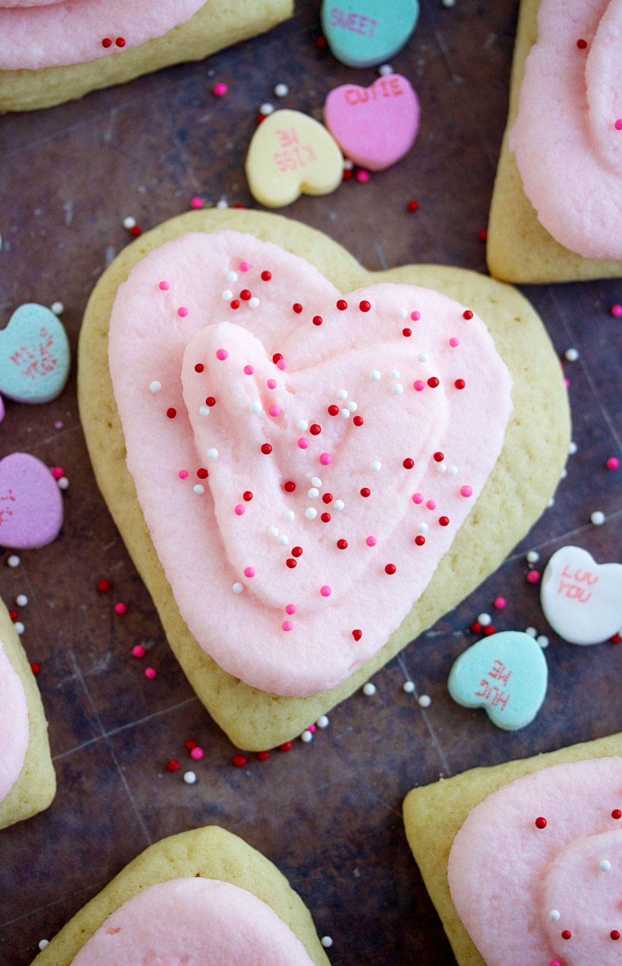 overhead shot of a heart-shaped sugar cookie with pink frosting and sprinkles