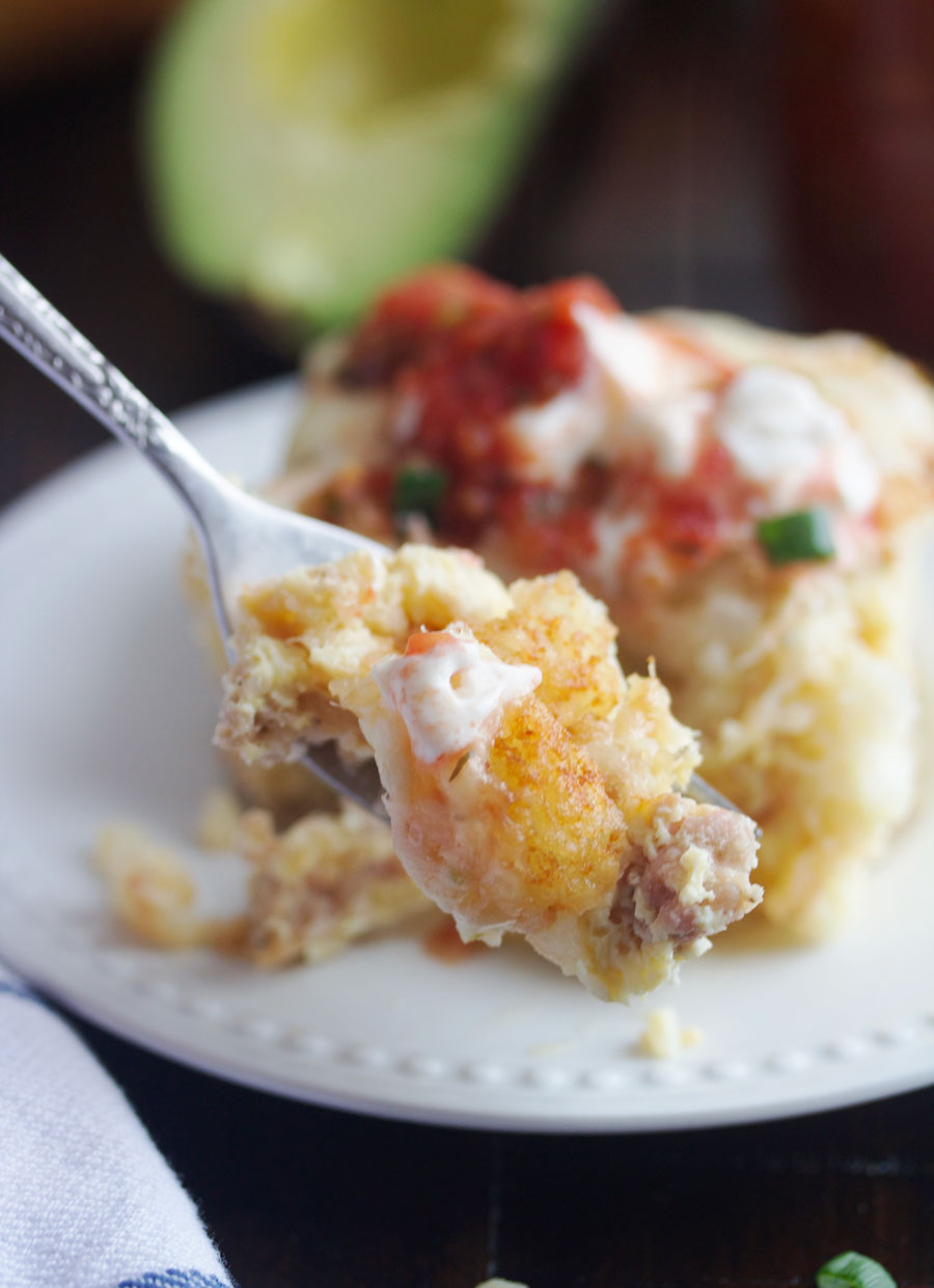 tater tot breakfast casserole with some on a fork and a plate of it behind the bite on the fork.