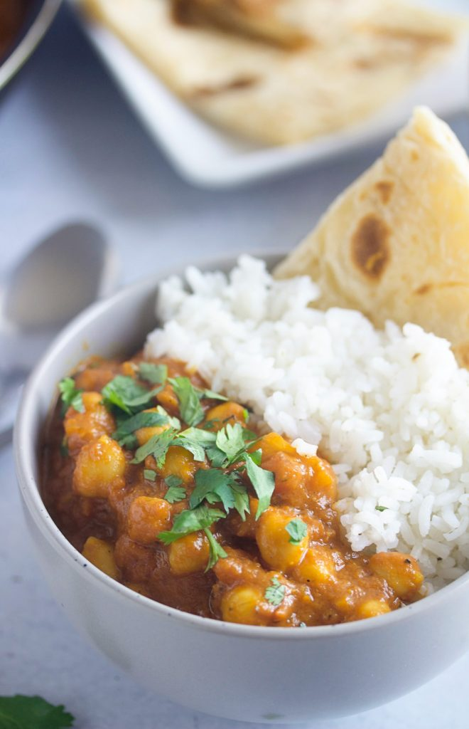 Bowl of coconut chickpea curry with white rice and flatbread