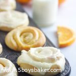 orange rolls in a muffin tin with a glass of milk and orange slices in the background