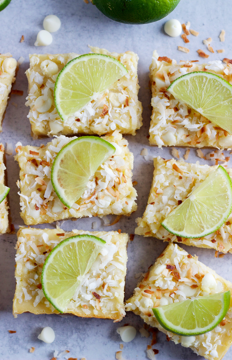 White chocolate coconut lime bars with a thin slice of lime on top of each and laying on a gray background