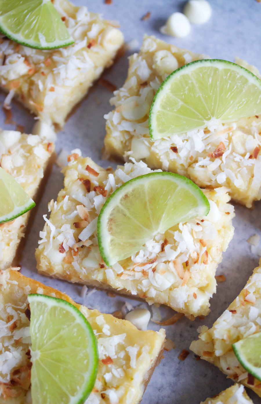 overhead shot of white chocolate coconut lime bars with a thin slice of lime on top of each squre