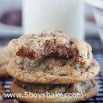 three chocolate chip cookies stacked on top of each other with a glass of milk behind them