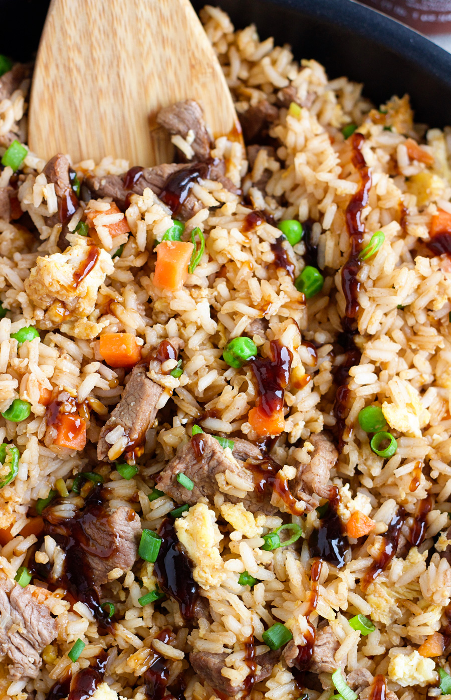 up close shot of a pan of steak fried rice with a wooden spoon in the pan