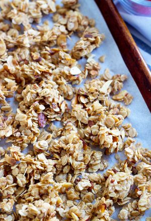maple-almond skillet granola on a cookie sheet with parchment paper
