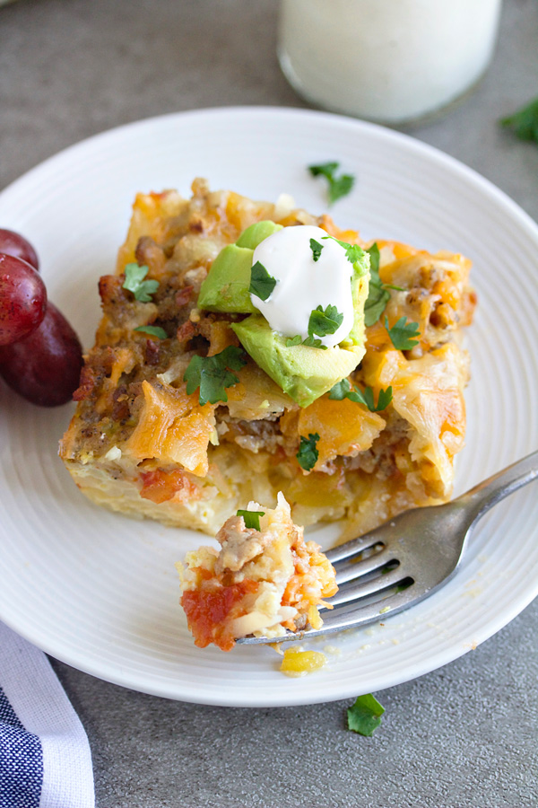 A piece of mexican breakfast casserole on a white plate with a bite on a fork sitting on the plate
