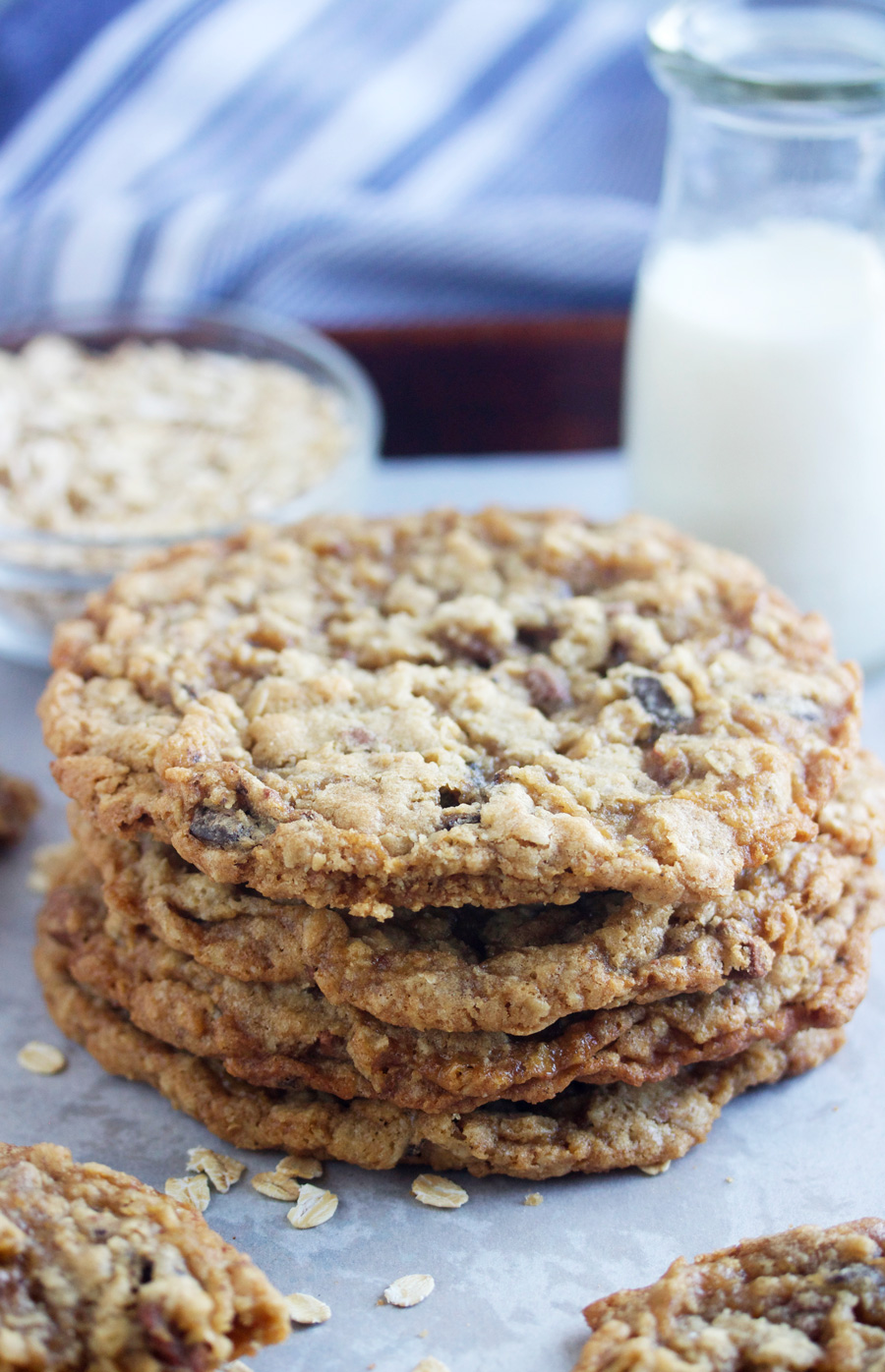 stack of pan banging oatmeal chocolate chip cookies with a glass of milk in the background