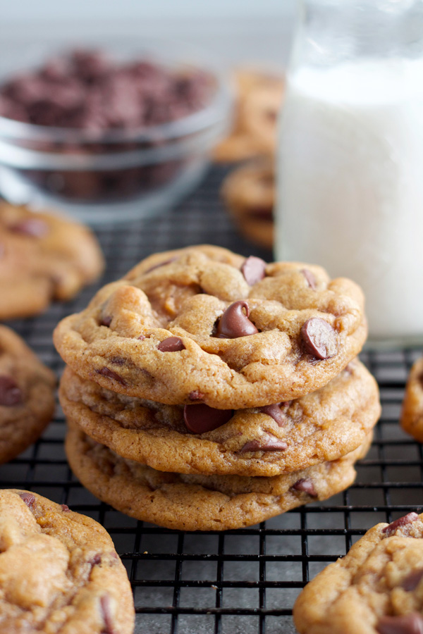 stack of three browned butter chewy pumpkin chocolate chip cookies with a glass of milk