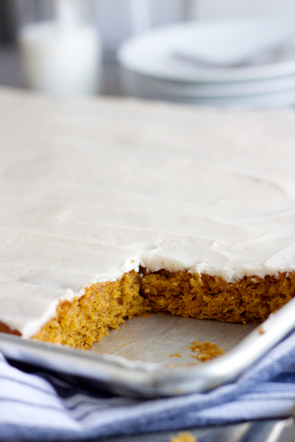 pan of pumpkin sheet cake with a few pieces cut out of it