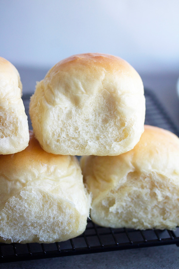 french bread dinner rolls stacked on top of a cooling rack