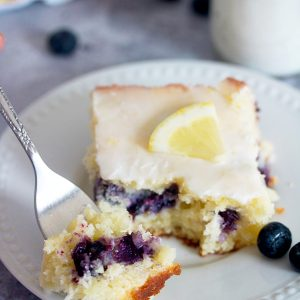 white plate with piece of blueberry lemon zucchini cake on it